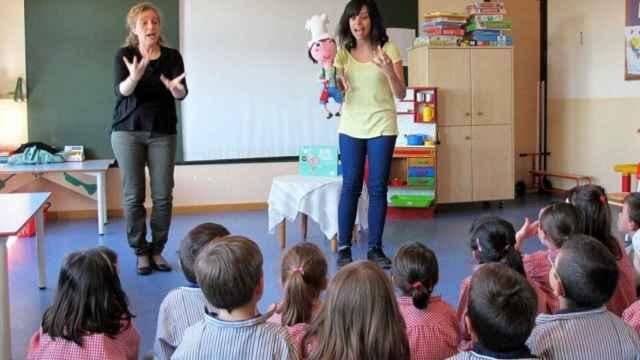 Una profesora explica, con ayuda de una intérprete de lengua de signos.
