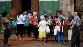 Cubanos haciendo cola frente a una bodega