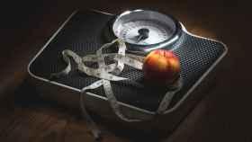 Una manzana y una cinta métrica sobre una báscula.