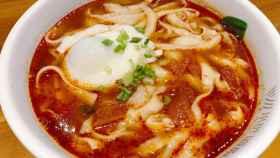 Una sopa de 'noodles' de huevo con tomate.