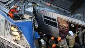Un equipo de bomberos intenta rescatar al maquinista atrapado en la cabina.