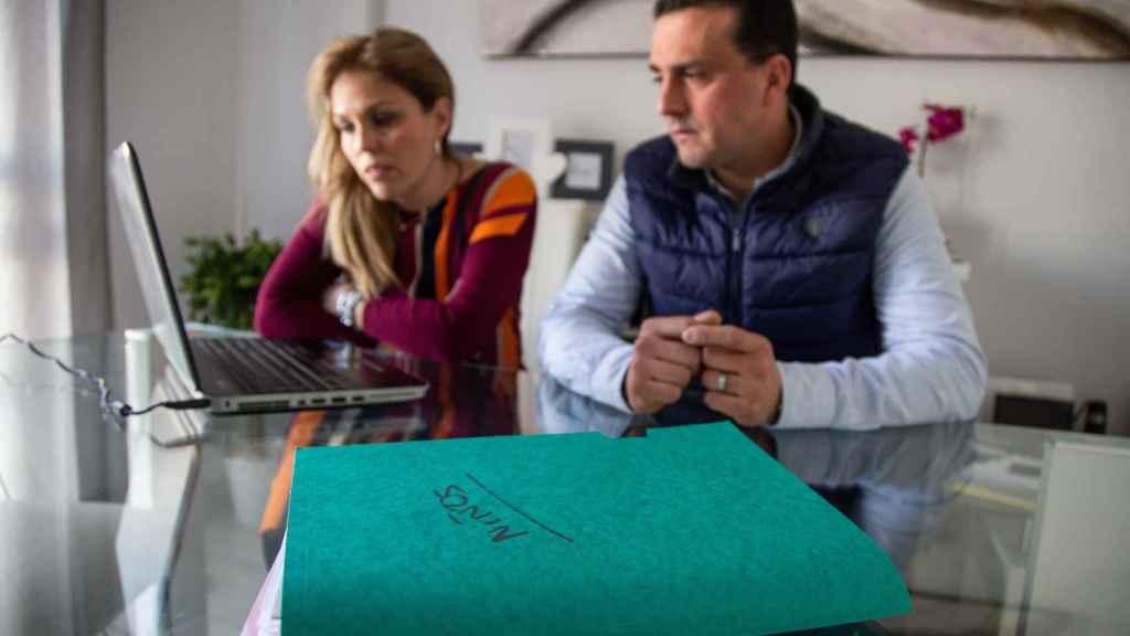 La pareja consultando la documentación del caso en el ordenador personal.