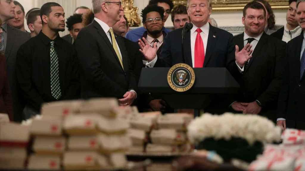 Donadl Trump habla frente a la mesa de hamburguesas