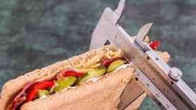 Una persona mide un sandwich vegetal con un calibre.