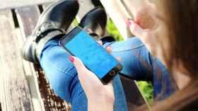 Una joven que consulta constantemente el teléfono móvil