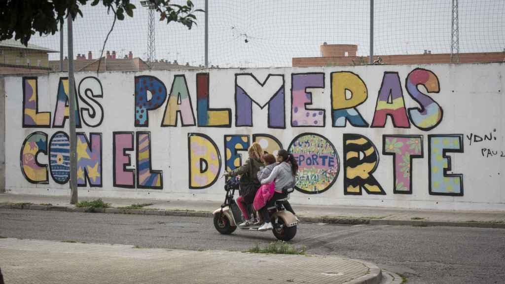 Una mujer conduce por la barriada cordobesa de Las Palmeras una moto con tres niñas menores de edad encima.