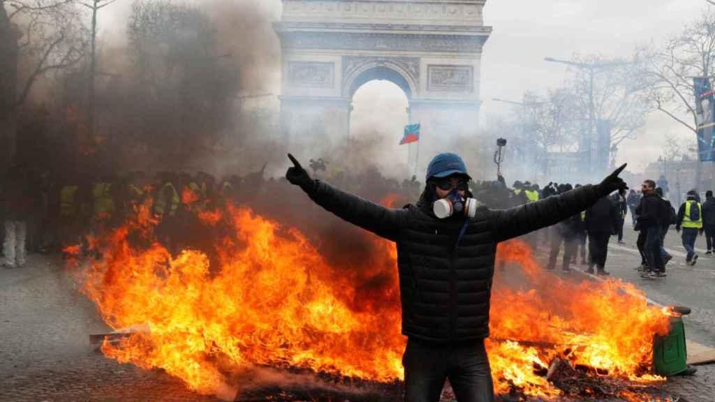Un manifestante se para frente a una barricada en llamas durante la manifestación de los 'chalecos amarillos' en París.