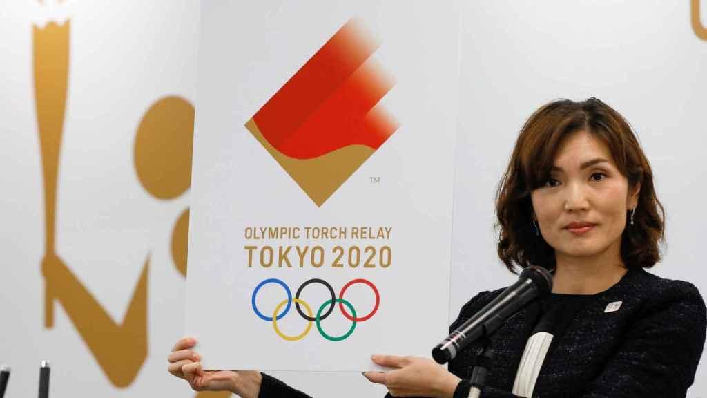 Miko Takeda, miembro del comité de relevos de la antorcha olímpica de los Juegos de Tokio 2020, muestra el emblema durante la ceremonia de presentación