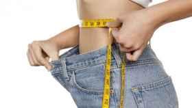 Una joven mide su cintura con una cinta métrica mientras se sujeta el pantalón.