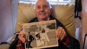 Charlie Galliano mostrando una foto en la que aparece (a la izquierda con corbata), junto a Lennon y Ono.