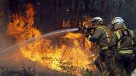 Los bomberos luchan por mitigar el incendio de Toques.