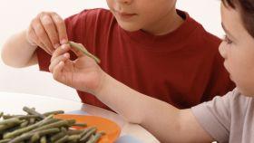 Unos niños comiéndose un plato de judías.