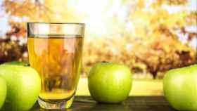 Un vaso de sidra junto a unas cuantas manzanas