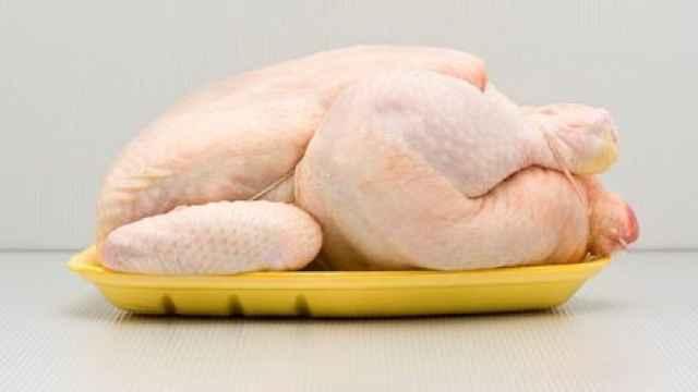 Un pollo de corral en una bandeja de supermercado.