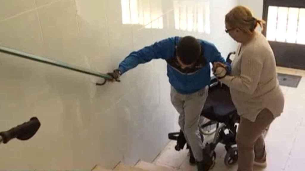 Vicenta ayudando a subir as escaleras a José Antonio, su hijo, con parálisis cerebral. Foto: Canal Extremadura