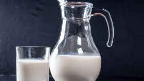 Una jarra llena de leche junto a un vaso.