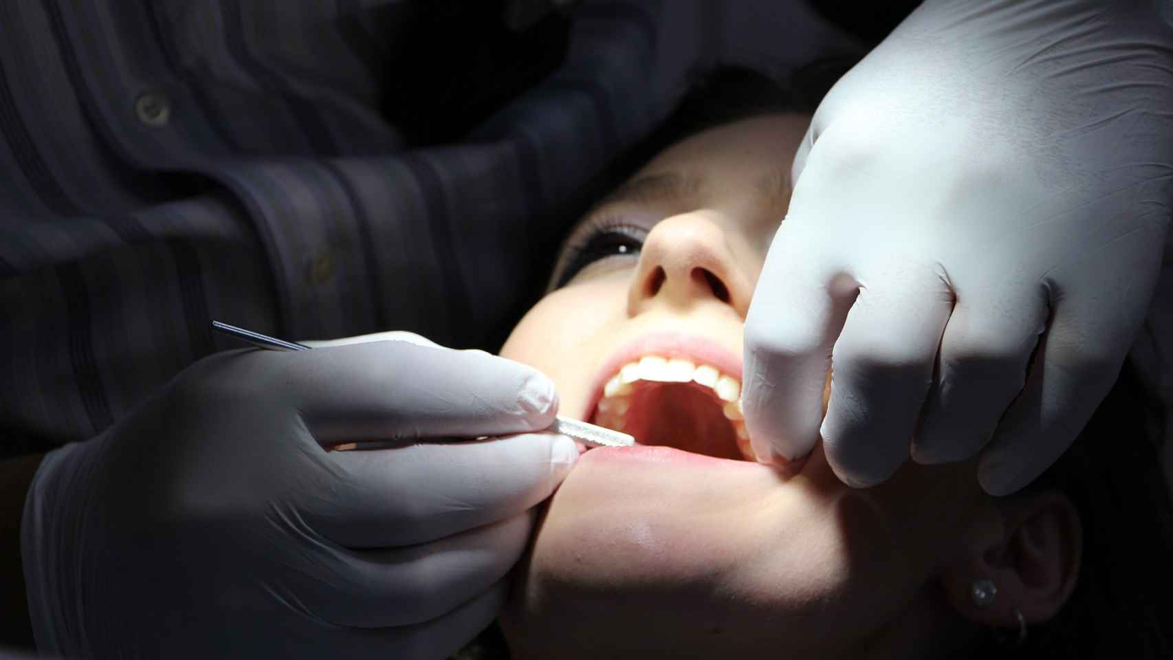 Una paciente es atendida por un dentista.