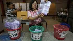 Una mujer sujeta una papeleta en una mesa electoral en Tailandia.