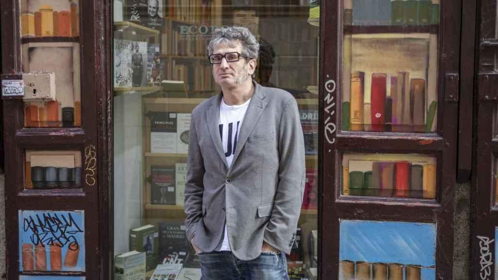 Camilo de Ory posa delante de la puerta de una librería.