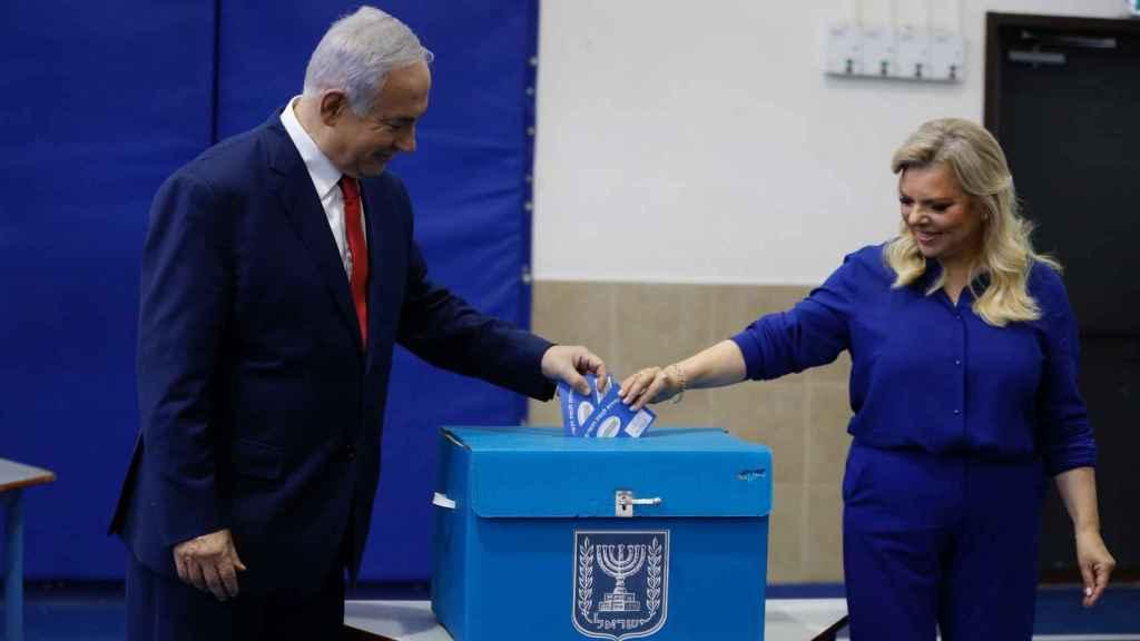 El primer ministro israelí, Benjamín Netanyahu, votando esta mañana junto a su mujer.