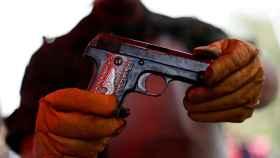 Un hombre sujeta un arma.
