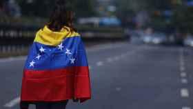 Una manifestante opositora recorre una calle desierta en Caracas