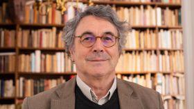 Andrés Trapiello en su casa, con su librería al fondo.