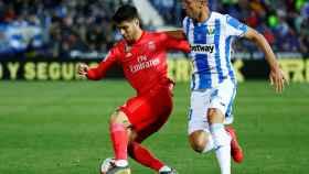 Marco Asensio defiende el balón ante Mikel Vesga