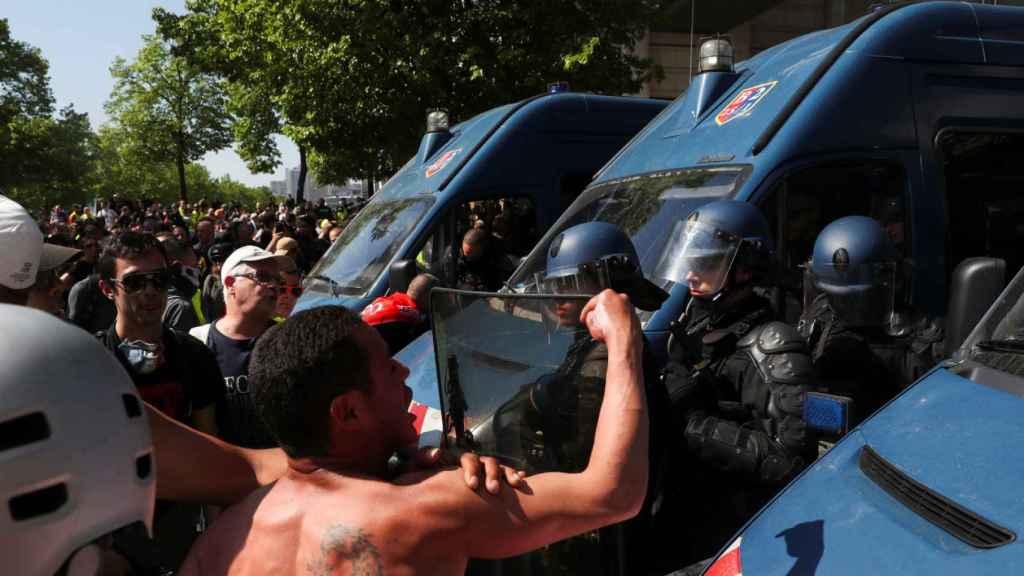 Un manifestante protesta ante varios agentes de la policía francesa este sábado.