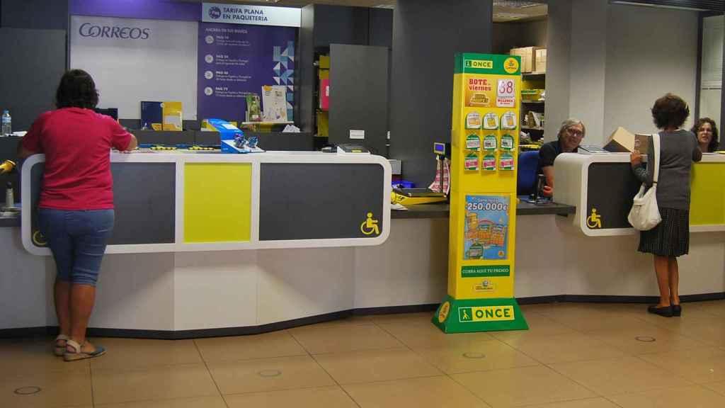 Una oficina de Correos con la publicidad de los productos de la ONCE.