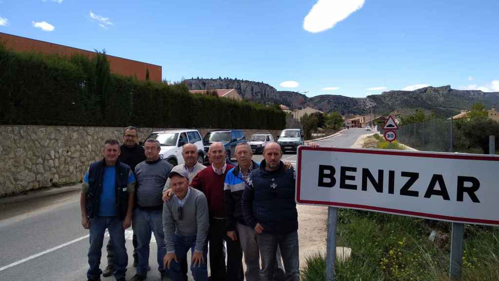 El alcalde pedáneo de Benizar junto al cartel del pueblo y varios vecinos.
