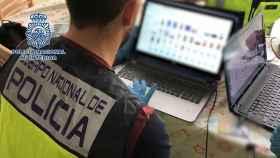 Un agente de Policía Nacional inspecciona un ordenador en una operación contra la pederastia.