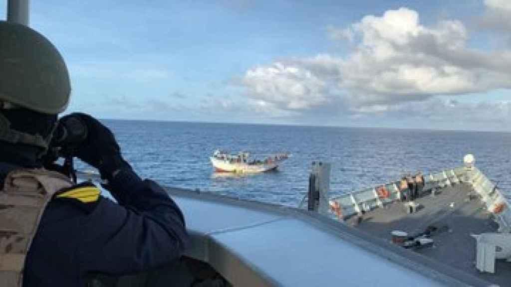 Un miembro de la dotación de la Navarra estudia los movimientos del barco tomado por los piratas.