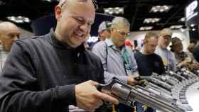 Un hombre maneja un revólver Smith & Wesson, durante la reunión anual de la NRA en Indianápolis.