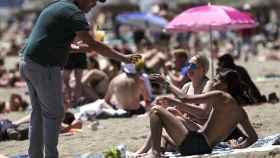 Una pareja es atendida por un vendedor ambulante en la playa de la Málagueta. Jorge Zapata / EFE