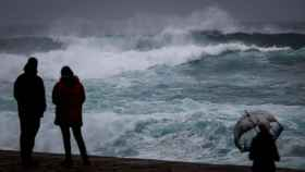 Varias personas observan el mar este sábado en San Sebastián. EFE/Javier Etxezarreta.