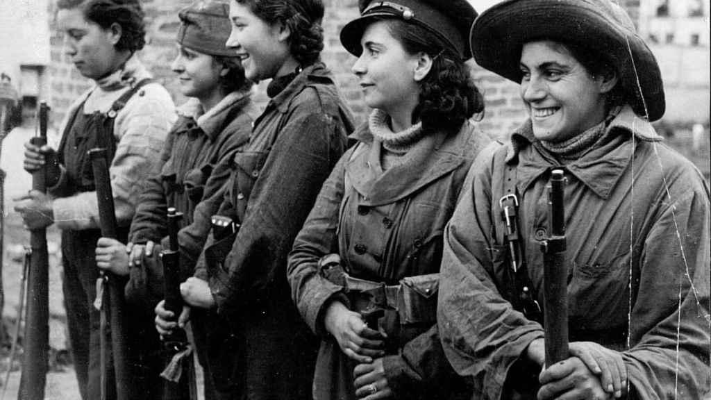 Un grupo de jóvenes mujeres forman sosteniendo unos fusiles.