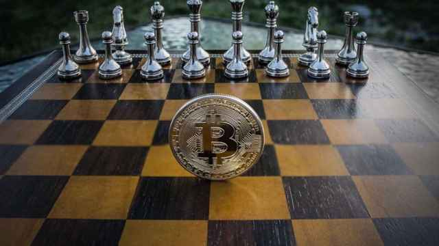 Una moneda de bitcoin en un tablero de ajedrez.