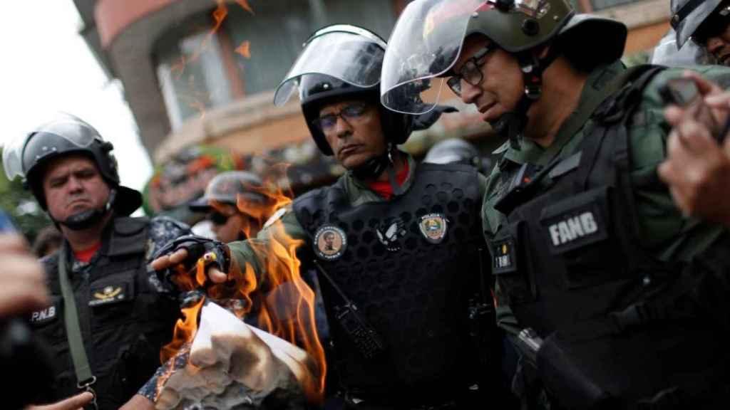 Un miembro de la guardia nacional quema el documento escrito por Juan Guaidó cerca de una base militar en Caracas.