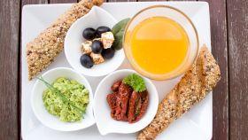 Un desayuno elaborado con zumo de naranja y pan integral.