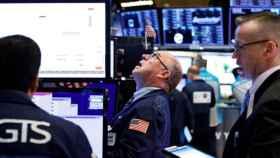 Varios operadores consultan pantallas de cotización en Wall Street.