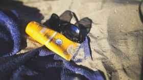 Una toalla, arena, gafas y una crema solar