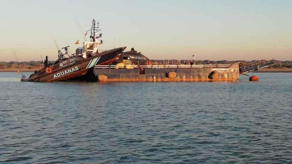 El barco 'Águila 2' de Vigilancia Aduanera, encallado en una gabarra en un operativo en el Guadalquivir.