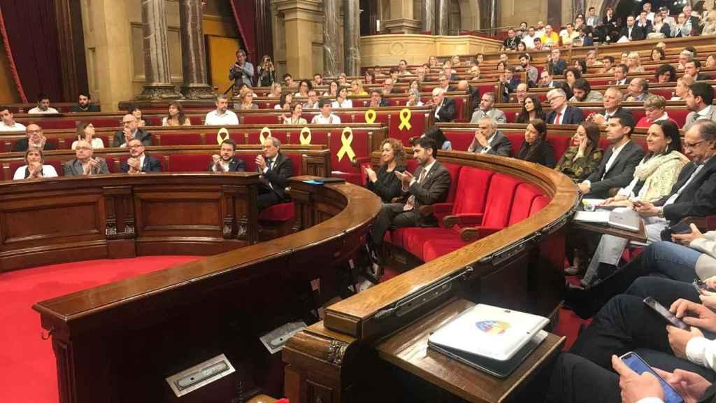 Imagen del Parlament con los lazos amarillos en los escaños vacíos