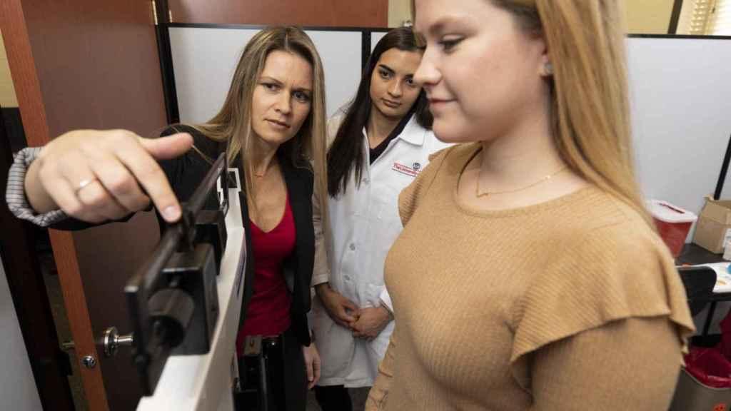 La prof. Cooper junto a una alumna de doctorando pesando a una de las participantes en el estudio.
