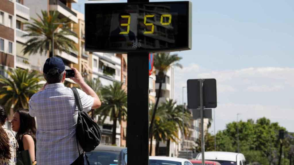 Un turista fotografía un termómetro de una calle de Córdoba que marca 35 grados. EFE/Salas.