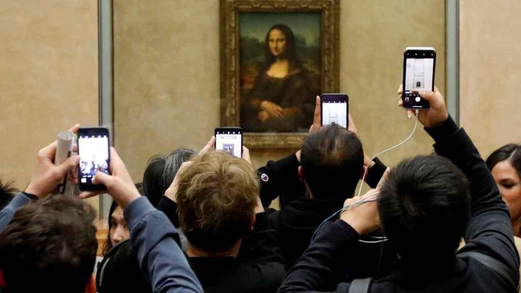 Visitantes del Louvre fotografían a 'La Gioconda' con sus teléfonos móviles.