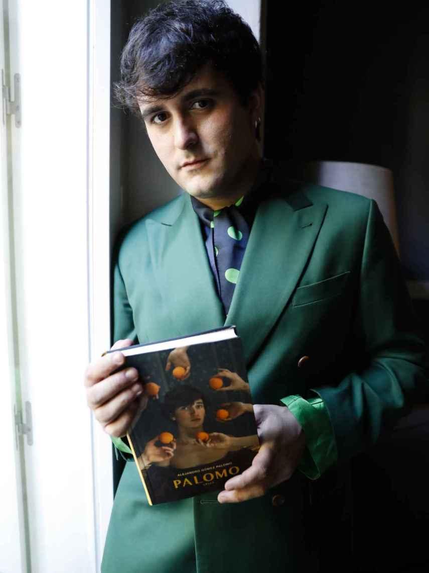 El diseñador posando con su libro en la mano.