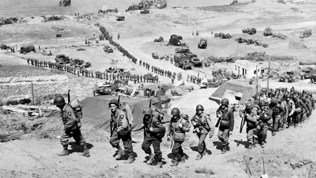 Tropas estadounidenses tras desembarcar en Normandía pasan al lado de un búnker alemán.