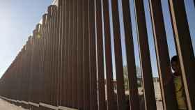 Un niño mira a través del muro que separa la frontera entre EEUU y México.